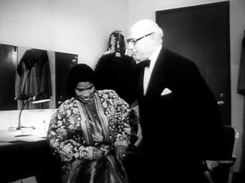 vídeos de stock e filmes b-roll de medium shot contralto singer marian anderson talking to her manager sol hurok in dressing room backstage/ usa - sentar se
