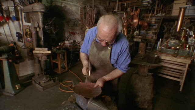 Medium shot coppersmith banging copper plate with hammer in workshop in Montepulciano / Tuscany, Italy