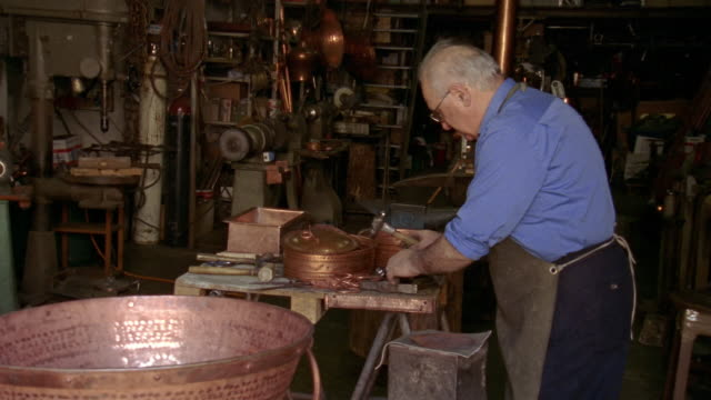 medium shot coppersmith hammering design on copper plate in workshop in montepulciano / tuscany, italy - montepulciano stock videos & royalty-free footage