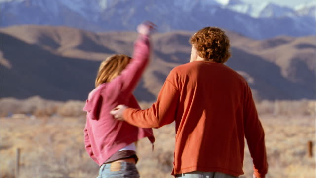 Medium shot couple arguing by roadside / hugging and getting back into car