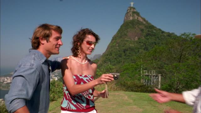medium shot couple asking man to take their photo / corcovado mountain / rio de janeiro - female with group of males stock videos & royalty-free footage