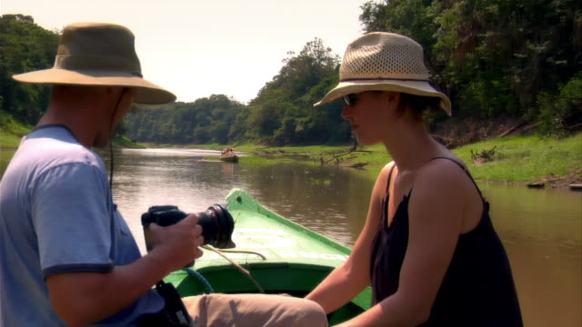 medium shot couple at front of small boat going up river as man takes photos/ the amazon, brazil - paar mittleren alters stock-videos und b-roll-filmmaterial