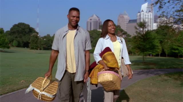 Medium shot couple carrying picnic baskets, lawn chair and blanket through Piedmont Park / Atlanta