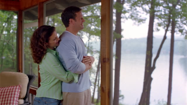 Medium shot couple cuddling and looking at view of lake from porch of lakehouse