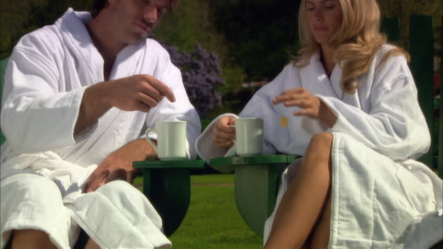 medium shot couple dipping teabags into mags and relaxing in deck chairs at spa/ monterey county, california, usa - ragged point stock videos and b-roll footage