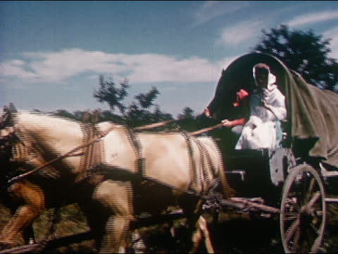 1963 REENACTMENT Medium shot couple dressed in 1800s style traveling across countryside in covered wagon / AUDIO