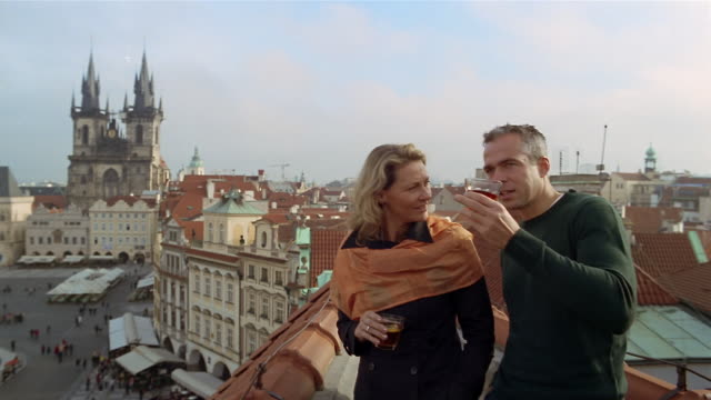 vídeos de stock, filmes e b-roll de medium shot couple drinking hot beverage on rooftop overlooking old town square / looking at view / prague - igreja de tyn