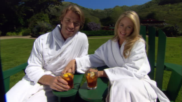 medium shot couple drinking ice tea and relaxing in deck chairs at spa/ monterey county, california, usa - ragged point stock videos and b-roll footage