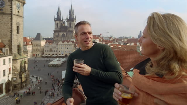 vídeos de stock, filmes e b-roll de medium shot couple drinking on rooftop overlooking old town square/ looking at view/ tyn church in background/ prague - igreja de tyn