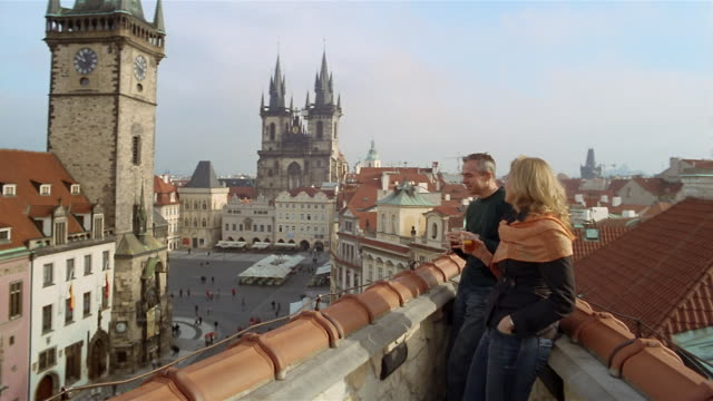 vídeos de stock, filmes e b-roll de medium shot couple drinking on rooftop overlooking old town square / looking at tyn church / prague - igreja de tyn