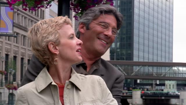 medium shot couple enjoying view from pedestrian bridge on riverwalk / pan across milwaukee river / milwaukee - 恋に落ちる点の映像素材/bロール