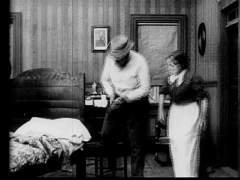 1910 B/W Medium shot couple getting ready for bed/ man putting sock filled with money under pillow