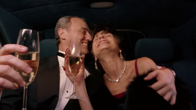 Medium shot couple in evening wear riding in limousine and drinking champagne / man kissing woman on cheek