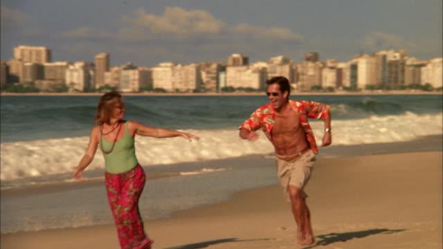 Medium shot couple kissing and running on beach