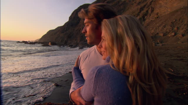 medium shot couple kissing on beach at sunset as tide comes in/ couple looking at camera/ couple walking away/ monterey county, california - ragged point stock videos and b-roll footage