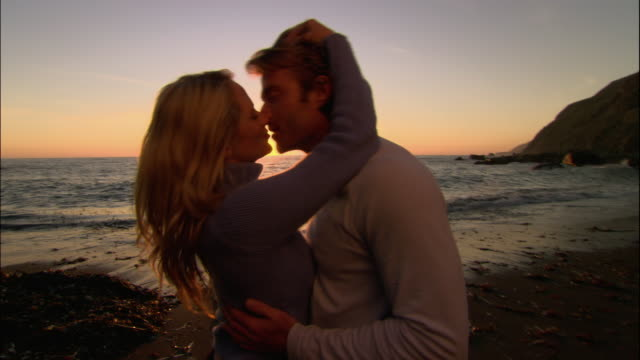 medium shot couple kissing on beach at sunset/ monterey county, california - ragged point stock videos and b-roll footage