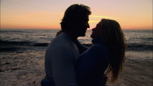 stockvideo's en b-roll-footage met medium shot couple kissing on beach at sunset/ monterey county, california - mid volwassen koppel