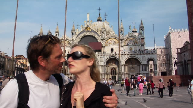 medium shot. couple kissing outside st. mark's cathedral in st. mark's square, venice, italy. - quarantenne video stock e b–roll