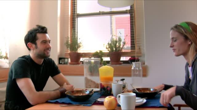 vídeos de stock e filmes b-roll de medium shot couple kissing over breakfast table/ new jersey - sentar se