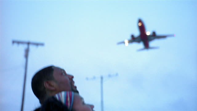 Medium shot couple looking up at jet / pan jet flying overhead at LAX / Los Angeles, California