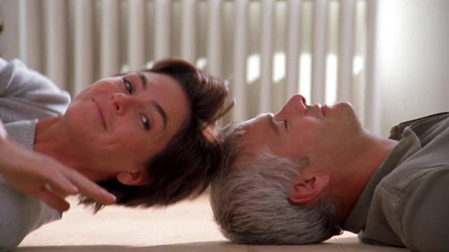 vídeos de stock, filmes e b-roll de medium shot couple lying head to head on their backs on floor / woman turning around and kissing man on nose - 40 49 anos