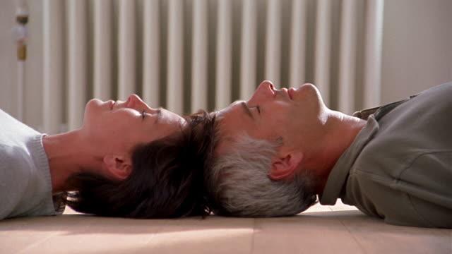 vídeos de stock, filmes e b-roll de medium shot couple lying head to head on wood floor w/eyes closed / couple laughing - 40 49 anos