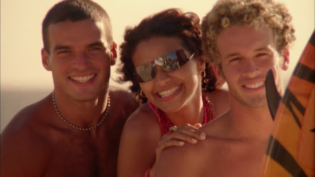 stockvideo's en b-roll-footage met medium shot couple on beach posing w/surfer and surfboard - ontbloot bovenlichaam
