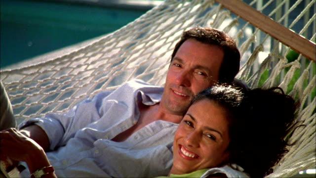 Medium shot couple relaxing on hammock