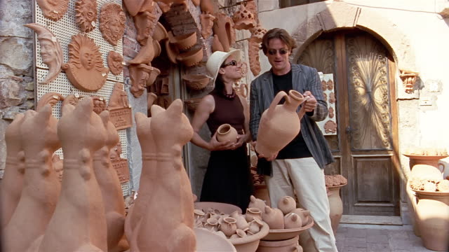 medium shot couple shopping for clay pots at pottery stand / sicily, italy - prodotti in ceramica video stock e b–roll