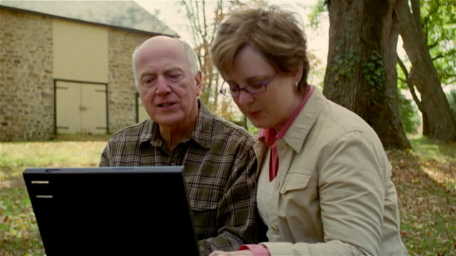 Medium shot couple sitting and working on laptop at picnic table/ Solebury, Pennsylvania