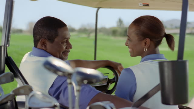 vídeos de stock, filmes e b-roll de medium shot couple sitting in golf cart / talking and laughing - camisa pólo