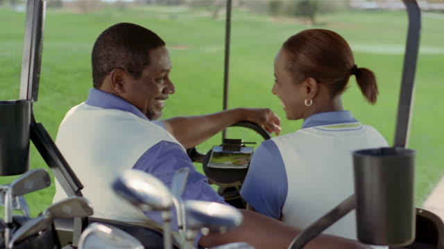 medium shot couple sitting in golf cart / talking and laughing - golf cart stock videos & royalty-free footage