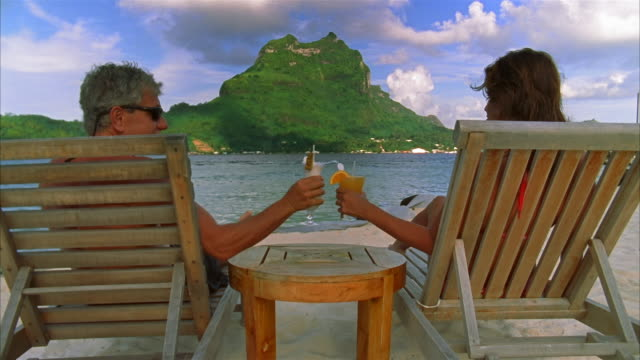 medium shot couple sitting in lounge chairs facing tree-covered mount otemanu / toasting with tropical drinks / bora bora - bora bora stock videos and b-roll footage