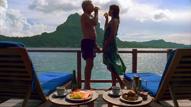 medium shot couple sitting on lounge chairs and standing up with mount otemanu in background / man pouring champagne into glasses / couple toasting / bora bora - パレオ点の映像素材/bロール