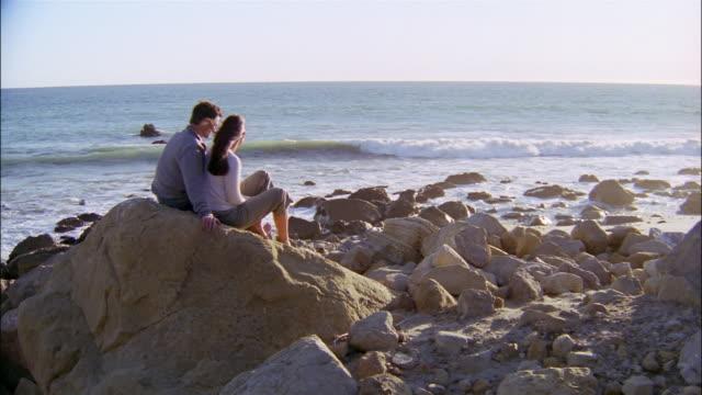 Medium shot couple sitting on rocks at the beach