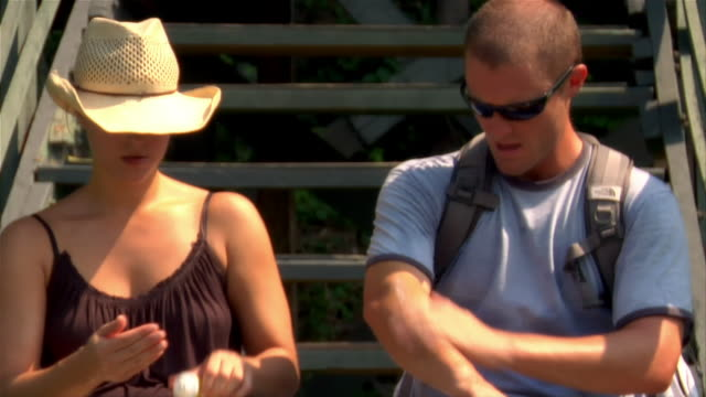medium shot couple sitting on steps applying sunblock/ the amazon, brazil - paar mittleren alters stock-videos und b-roll-filmmaterial