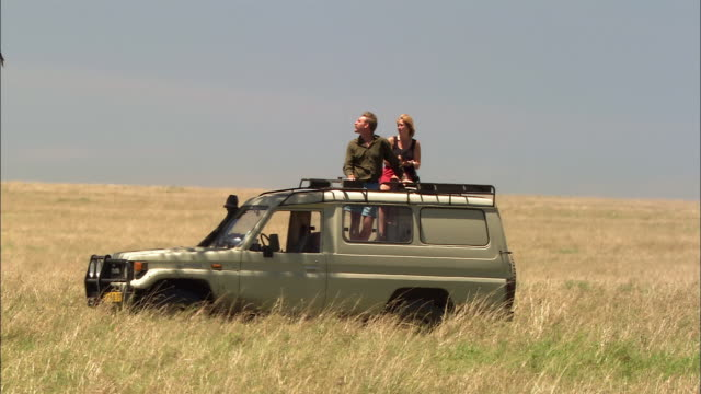 Medium shot couple standing up in back of safari vehicle and looking out of roof / Masai Mara, Kenya