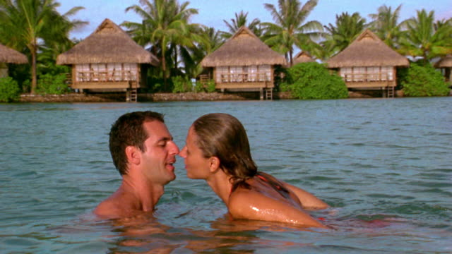 Medium shot couple swimming toward each other and kissing in water w/huts + palm trees in background