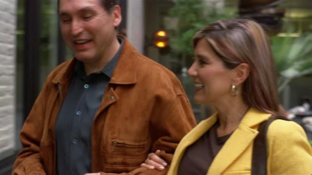 Medium shot couple talking and window shopping/ San Antonio, Texas
