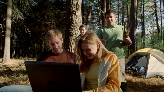 medium shot couple using laptop outdoors in woods / another couple approaching them and waving at webcam - land stock videos & royalty-free footage