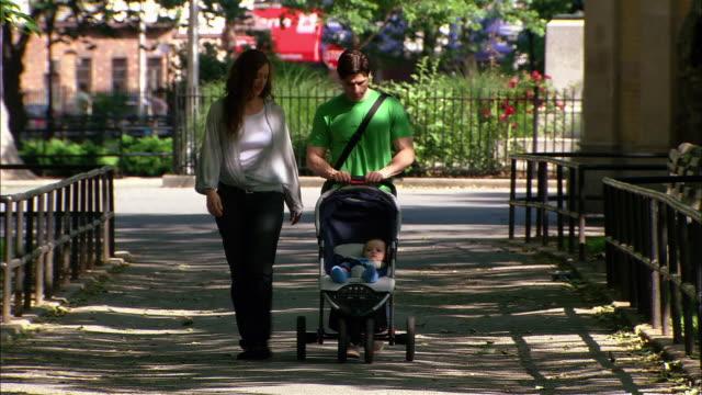 vídeos y material grabado en eventos de stock de medium shot couple walking along city street / man pushing baby in stroller - menos de diez segundos