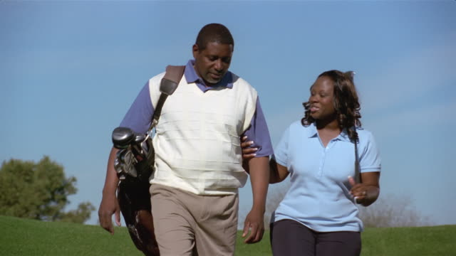 Medium shot couple walking arm-in-arm on golf course carrying golf clubs