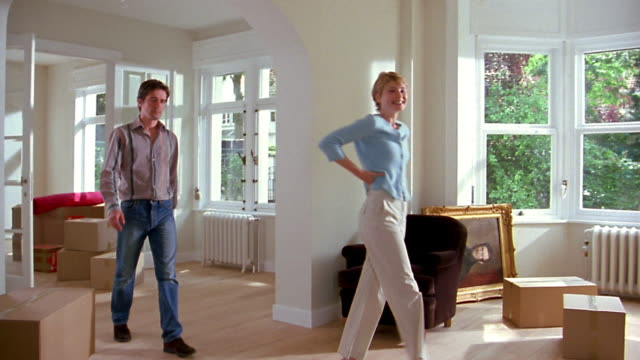 medium shot couple walking into living room / woman stretching her arms and walking  playfully / man gesturing - renovierung themengebiet stock-videos und b-roll-filmmaterial