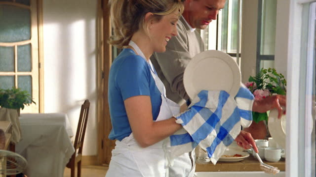 medium shot couple washing and drying dishes at kitchen sink / belgium - drying stock videos & royalty-free footage