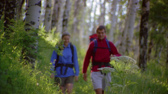 Medium shot couple w/backpacks hiking on rural trail and talking