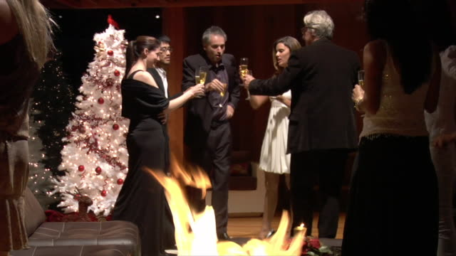 Medium shot Couples drinking a champagne toast and celebrating at Christmas party