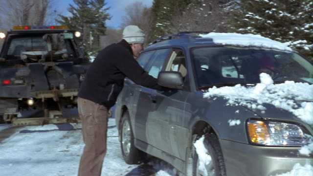 medium shot couple's station wagon stuck in snowbank / man talking to driver and tow truck driver / vermont - tow truck stock videos and b-roll footage