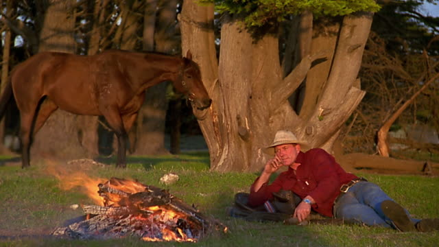 medium shot cowboy lying beside campfire / throwing log on fire / horse in background - 20 29 years stock videos & royalty-free footage