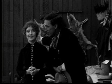 stockvideo's en b-roll-footage met 1915 b/w medium shot cowboy talking to and embracing woman  - cowboyhoed