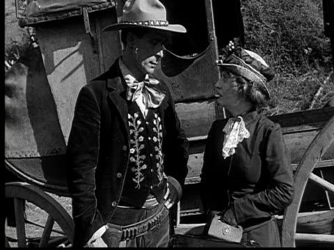 1915 b/w medium shot cowboy talking to woman crying near stagecoach  - 1915年点の映像素材/bロール